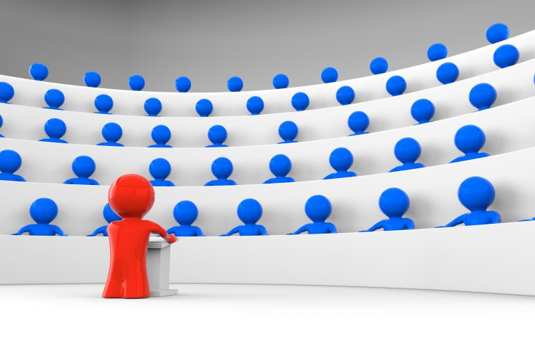 red character standing by a lectern facing an audience of blue characters sitting in five levels of tiered seating; shiny characters version; 3d rendering